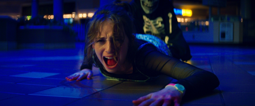 Maya Hawke in Fear Street Part 1. She is getting dragged across the floor in the film. Blue lighting baths the room and the skeleton hoodie and skull masked person is somewhat visible behind her.