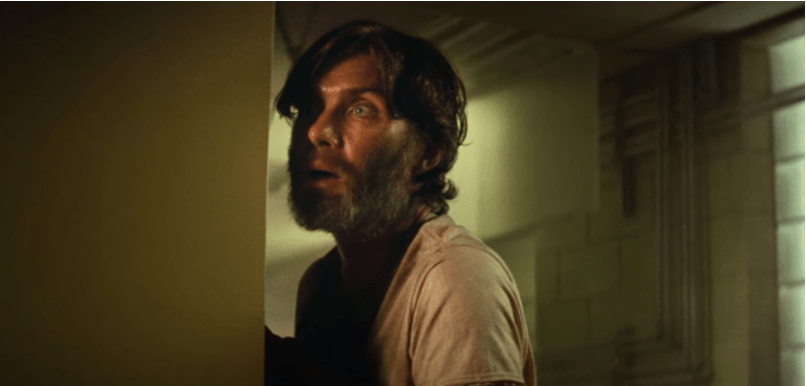 A still from 'A Quiet Place Part II'. Emmett (Cillian Murphy) is shown in close-up, centre frame. peering around the side of a wall in shock. The light hits his sweaty face, his overgrown beard covering lots of his face.
