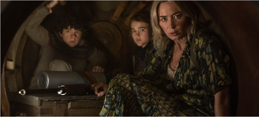 A still from 'A Quiet Place Part II'. Evelyn (Emily Blunt) is shown crouched in a tunnel with her daughter and son. She looks out at the camera, clutching a rifle down by her side, resting on top of a suitcase.