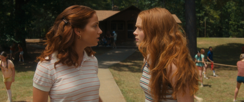 Emily Rudd and Sadie Sink as Cindy and Ziggy. They stand face to face as if they are arguing with the camp in full view behind them.