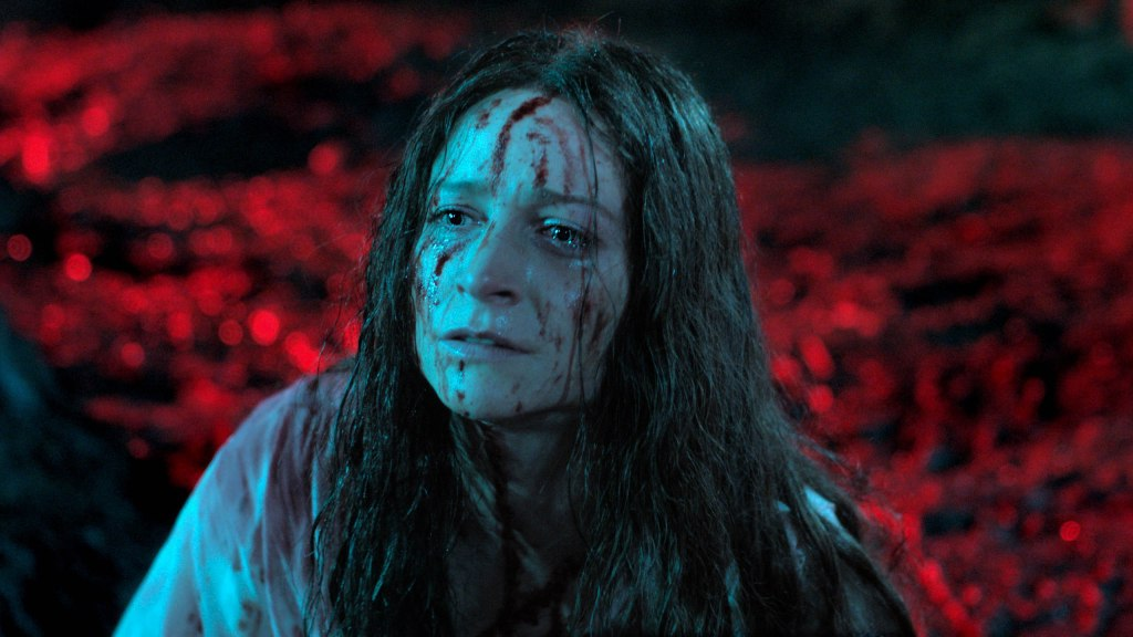 A woman kneels on a forest floor - it is night but the artificial lighting makes it appear red. Her face is covered in blood and the long, dark hair is matted with it as well.
