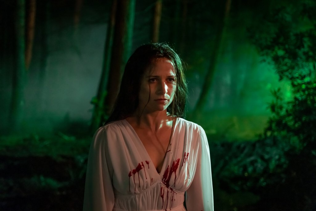 A still from 'Censor'. Enid (Niamh Algar) is shown in a mid-shit, centre frame, in a forest backlit by green light. She wears an elegant flowing white gown with a splatter of blood across her chest. Her long brown hair is wet, she looks determined.