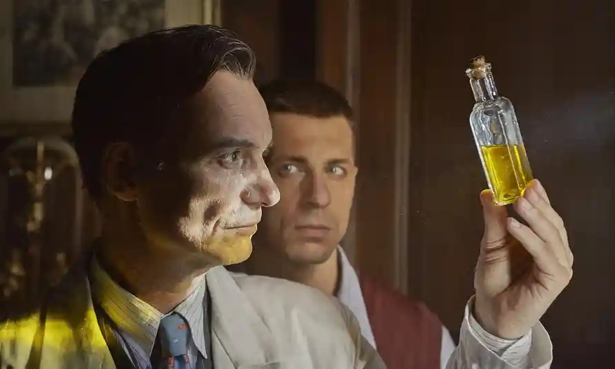 A still from 'Charlatan'. Jan Mikolášek is shown in close-up, in profile, holding a small square bottle full of urine, which he is holding up to the light, the yellow twinge reflecting back on his face. He is a white man in his 40s/50s with slicked back brown short hair and wearing a lab coat and pinstripe shirt and tie. His assistant stands behind him looking on.