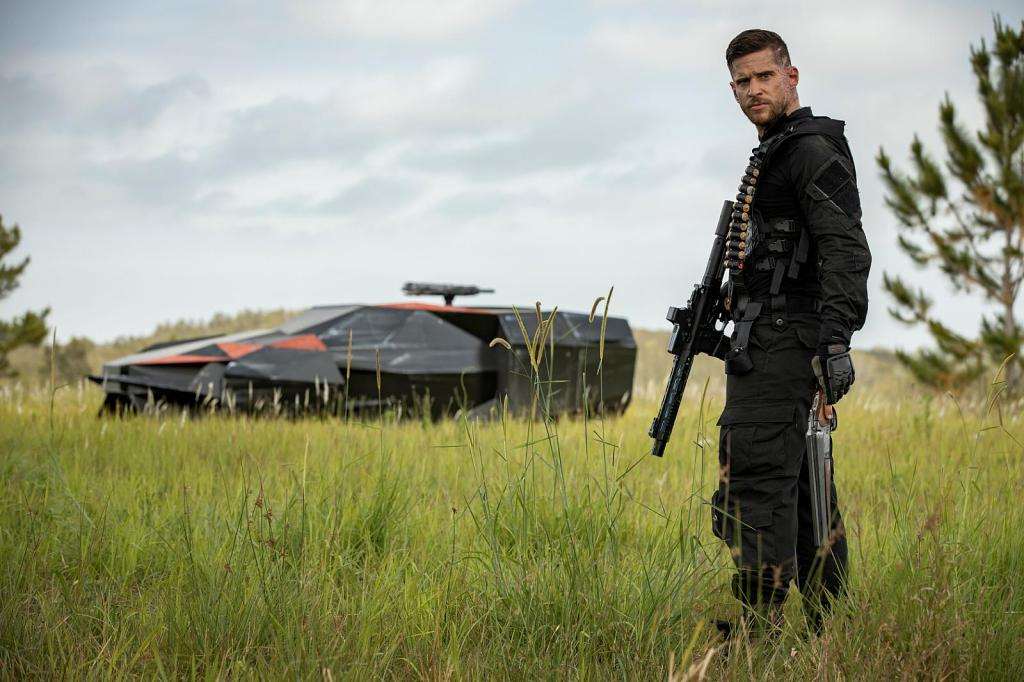 A still from 'Occupation: Rainfall'. Matt Simmons (Dan Ewing) is shown in a wide shot to the right of the image, in full black military gear, loaded with guns and ammo. He is a white man with his hair short and a small amount of facial hair, his expression is concerned. In the meadow behind him is a black and orange spacecraft, parked in the grass.