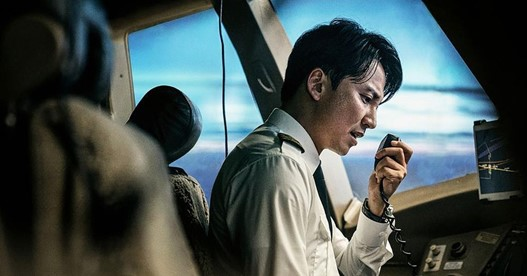 Still from Bi-Sang-Seon-Eon. A pilot is holding a radio up to his face and talkng into it. In the background, the clouds and blue sky are clear through the cockpit windows.