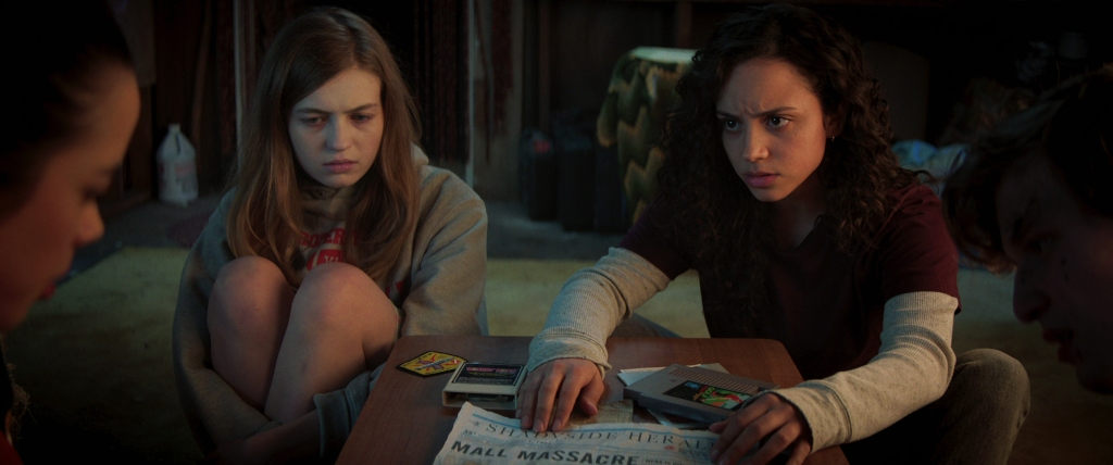Julia Rehwald and Olivia Welch and two others looking concerned over a newspaper.
