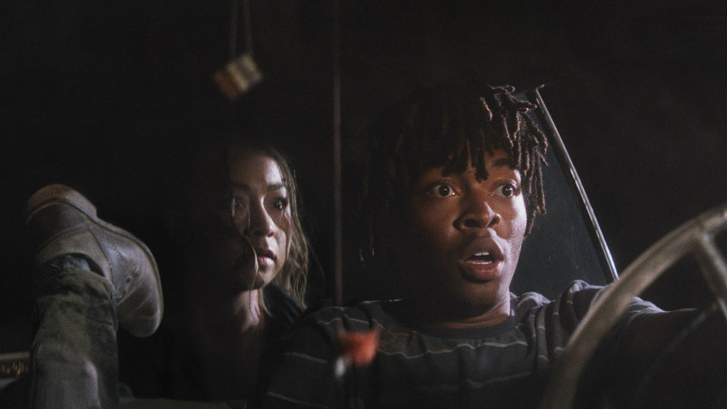 Still from First Date. In the foreground is Mike (Tyson Brown), sitting in the front of a car in the driver's seat. His eyes are wide in panic, as he looks out the window at something unknown.  To his left is a leg sticking up, only the shoe and ankle visible.  Behind him sits Kelsey (Shelby Duclos), her face is lit up by an outside light and she looks similarly shocked. It is nightime, and the surroundings are pitch black.