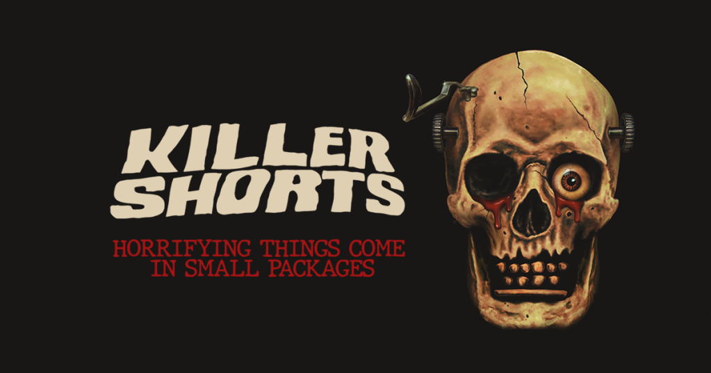 Poster for Killer Shorts. Killer Shorts is in a wavy white font i the middle of the image on a black background. Underneath is 'Horrifying Thing Come in Small Packages' in a red, blocky font underneath. To the left is  as weathered skull with blood coming from the eye sockets - one has an eyeball in it. There are bolts through the temples.