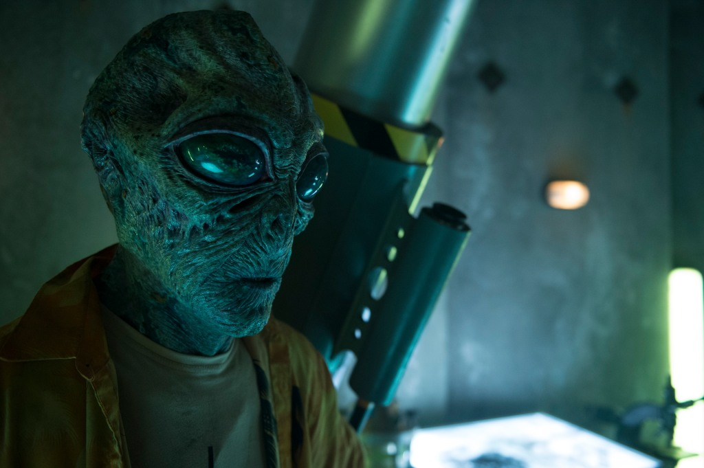 A still from 'Occupation: Rainfall'. A grey alien is shown in a mid shot, to the left of the image, on board a space craft. He has large eyes and wrinkled skin, and a small mouth. He wears a brown t-shrit and darker brown jacket.