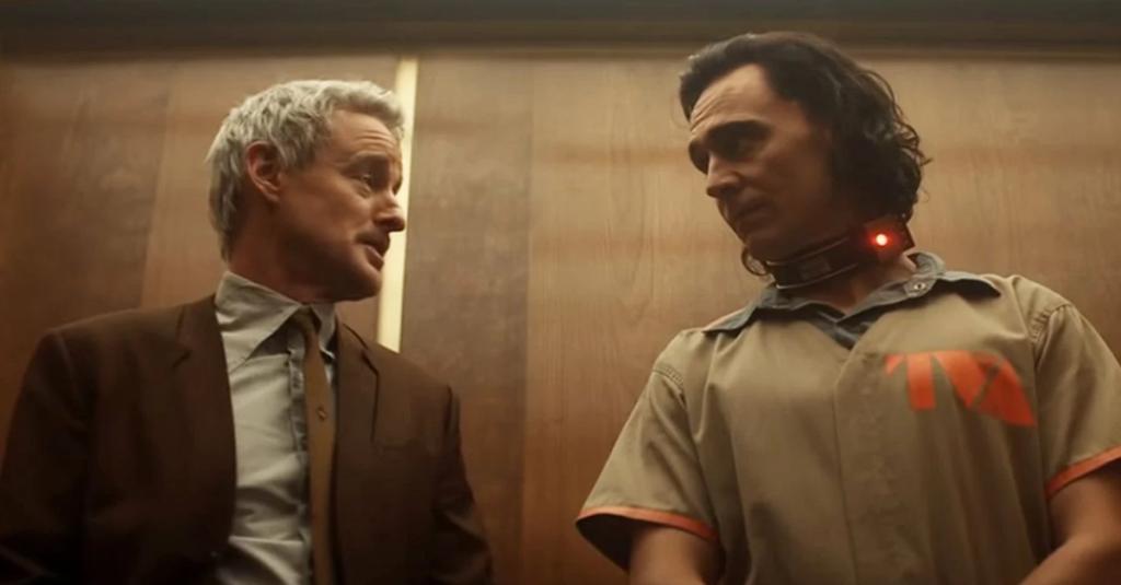 A still from TV show 'Loki'. Mobius (Owen Wilson) is stood in a corridor against a wooden backdrop with Loki (Tom Hiddleston), who is dressed in TVA Prisoners uniform with a metal collar around his neck, flashing a red light. Mobius is wearing a brown suit and is mid-conversation.