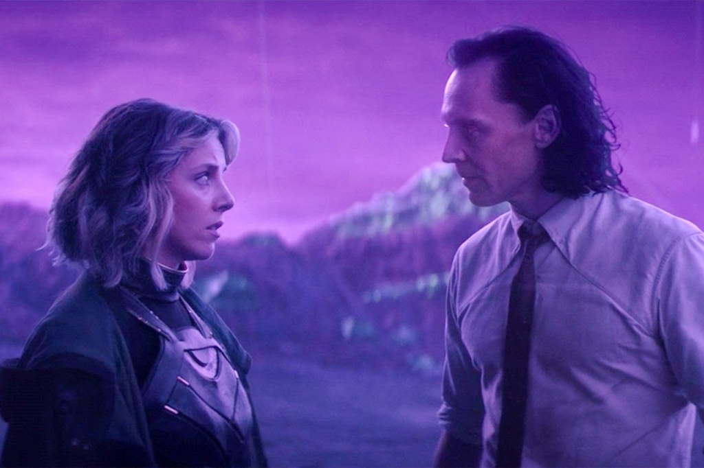 A still from TV show 'Loki'. Loki (Tom Hiddleston) is stood next to his variant self Sylvie (Sophia di Martino) in a hazy purple backdropped landscape, that almost looks unreal. She is wearing full Loki costume, but with short blonde hair, and he is wearing a white shirt and thin, red tie.