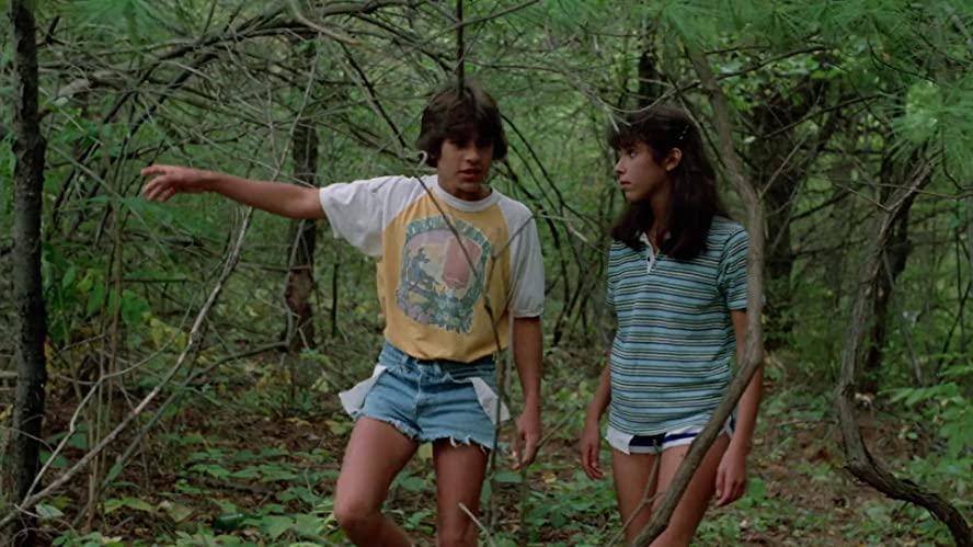 Still from Sleepaway Camp (1983). A pair of teenagers, Angela and Ricky, in cut-off shorts and t-shirts, wander through a dense forest together, seemingly alone.