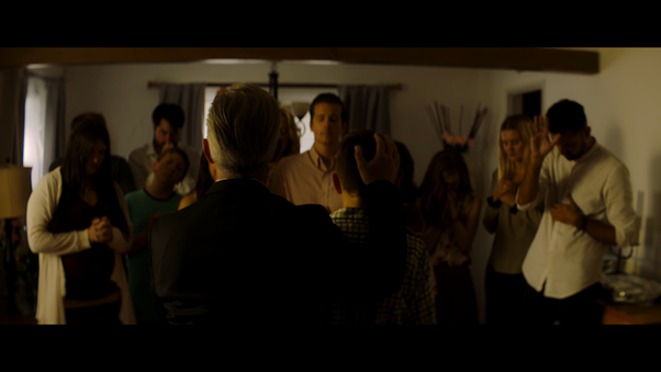 Still from 'The Body of Levi' - a group of people of varying ages stand in a room, facing a man who has his back to the camera, with one hand on the head of a ypung boy. The crowd have their hands lifted in prayer and healing.