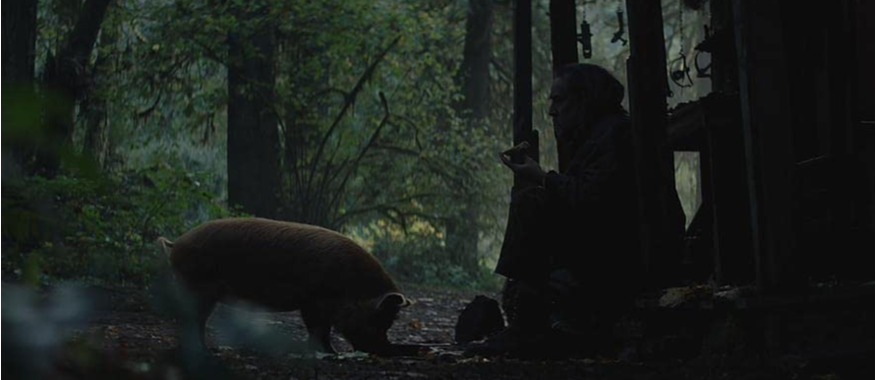 A still from 'Pig'. Robin (Nicolas Cage) is shown in a wide shot, sat on the floor of a rough cabin, a truffle pig is on the floor sniffing the ground next to him. They are in a forest setting and the image is dark and still.