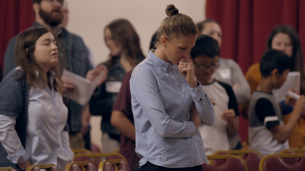 A still from documentary 'Pray Away'. A woman in a blue shirt with her hair in a tight bun is shown in the middle of a church service, deep in thought, her hand to her mouth and other arm folded. Blurred behind her are many other congregants, deep in the process of worship.