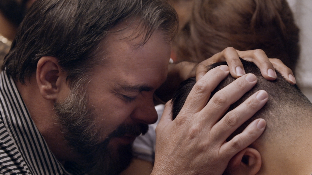 A still from documentary 'Pray Away'. A middle-aged bearded man is shown in close-up, praying with his hands on the head of a young boy.