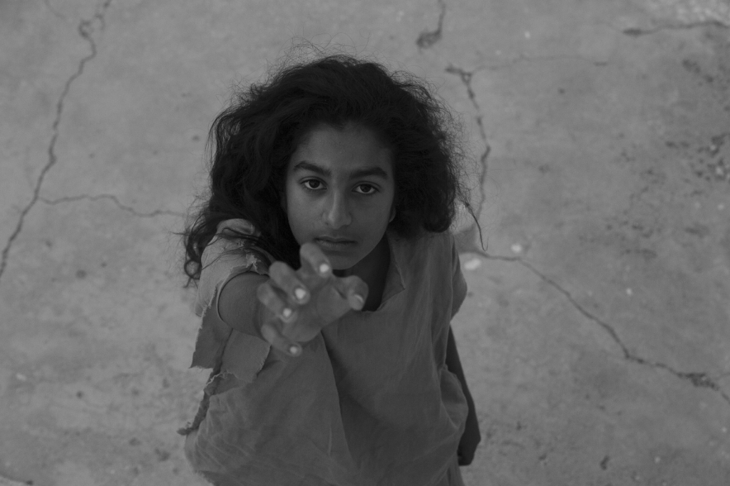 A still from 'Scales'. A Black and white image of a young, middle-eastern girl staring directly up the lens, shot from above her eyeline, reaching out with one arm. Her clothes are basic and her hair is wild.