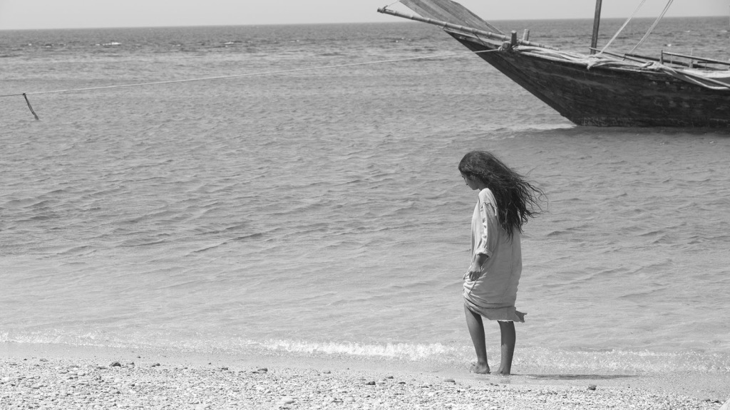 A still from 'Scales'. A young girl with wild black curly hair, wearing a tunic, walks along a beach, a wrecked ship is just in the background of the right hand side of the image.