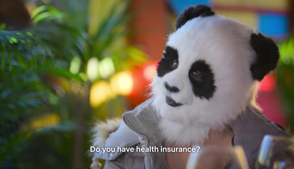 A still from reality tv show 'Sexy Beasts'. A woman in Panda prosthetics is shown in close up, in a restaurant. Captions on the bottom of the image read 'Do you have health insurance?'