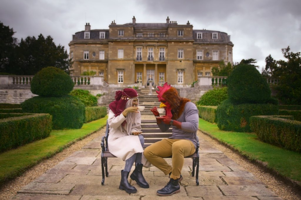 A still from reality show 'Sexy Beasts'. A woman in fortune teller prosthetics and a man in chicken prosthetics are sat on a bench drinking tea outside a country mansion.
