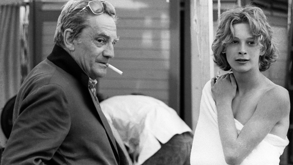 Picture from the set of Death in Venice. Luchino Visconti stands on the left of the image, a cigarette in his mouth with his sunglasses pushed back on his head.  Björn Andrésen, as a 16 year old is standing next to him, a towel wrapped around his naked torso.
