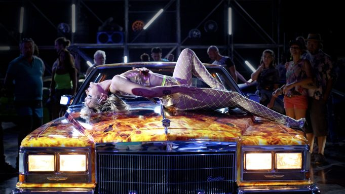 A woman  lies on the bonnet of a car, her back arched towards the celings, legs spread in a provocative manner. She is dressed in underwear and neon yellow fishnets. The car is covered in flames. People in the background are watching, as the spotlights are focused on hers.