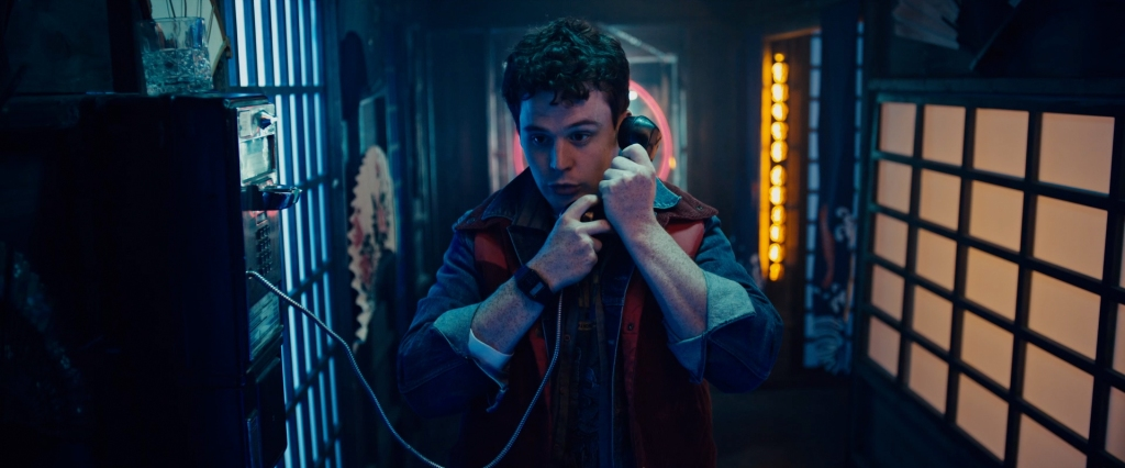 A still from 'Vicious Fun'. Joel (Evan Marsh) is pictured in a mid-shot, centre frame, using a payphone and dressed as Marty McFly. He is in a Chinese restaurant and the lighting is drenched in neon.