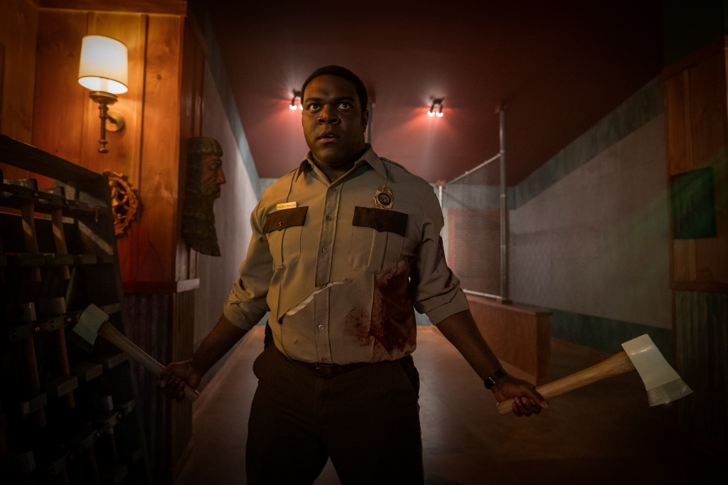 A still from 'Werewolves Within'. Finn (Sam Richardson) is shown inside a dated room in a dreary Inn. He is a park ranger, dark skin and his shirt is bloodied. He wields an axe in each hand and is standing ready to fight.