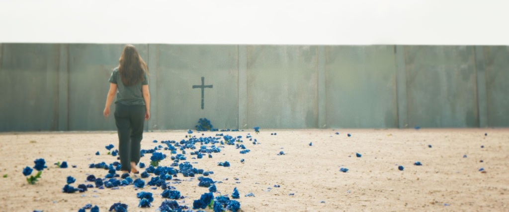 A still from 'Witch Hunt'. A young woman is shot in a wide, to the left of the image, walking along a bed of blue petals in a desolate environment. A crucifix is fixed to the wall she is walking towards.
