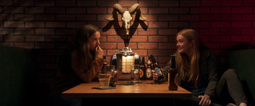 A still from 'Witch Hunt'. Two teenage girls sit at a booth in a dimly lit bar, a goat's head skeleton above their table. They are drinking beer and chatting intently.