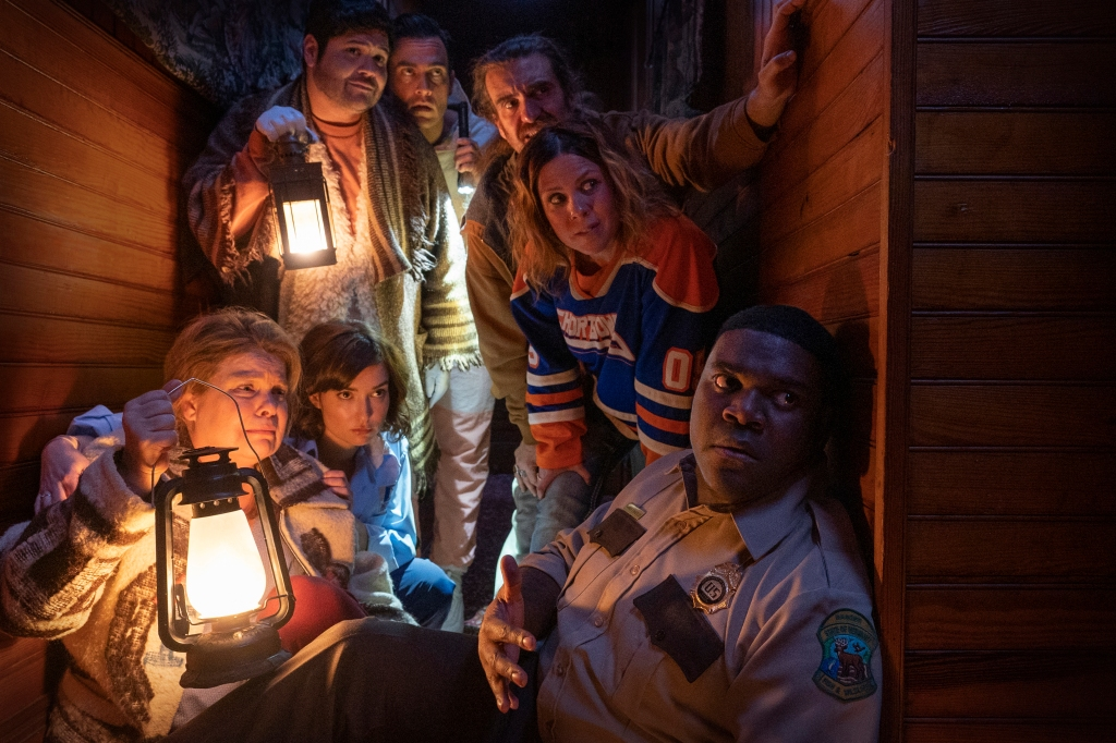 A  still from 'Werewolves Within'. A rag tag group of misfits are shown hiding behind a shed, two people are holding lanterns which is the only light to show their faces. A police officer is in the forefront, peering around the shed.
