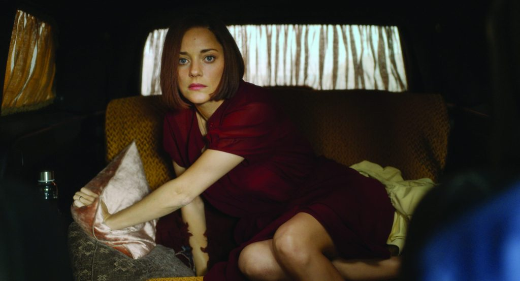 A still from 'Annette'. Ann (Marion Cotillard) is shown in a mid-shot, in the back of a car with curtains pulled across the windows. There is pillows and blankets on the back seat, she has been sleeping there. Ann wears a short puffed sleeve deep red dress and has a ginger bob. She looks directly at the camera.