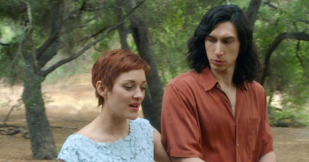 A still from 'Annette'. Ann (Marion Cotillard) and Henry (Adam Driver) are shown in a close-up, walking through a warm landscape, sandy floors and trees behind them. Ann is speaking and is much shorter than Henry, she wears a floral blue dress and her ginger hair is cropped in a pixie cut. Henry is very tall, wearing a burnt orange shirt and has long black hair, he looks to Ann as she speaks.