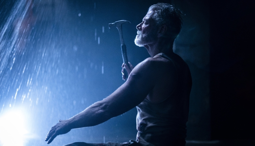 A still from 'Don't Breathe 2'. Norman (Stephen Lang) is shown in a mid shot, centre frame, in profile. He is an older man in his 50s/60s, with grey hair and beard wearing a vest. He holds a hammer in his right hand and has his left outstretched. His eyes are closed and the image is shrouded in a blue light, it is difficult to tell where he is.