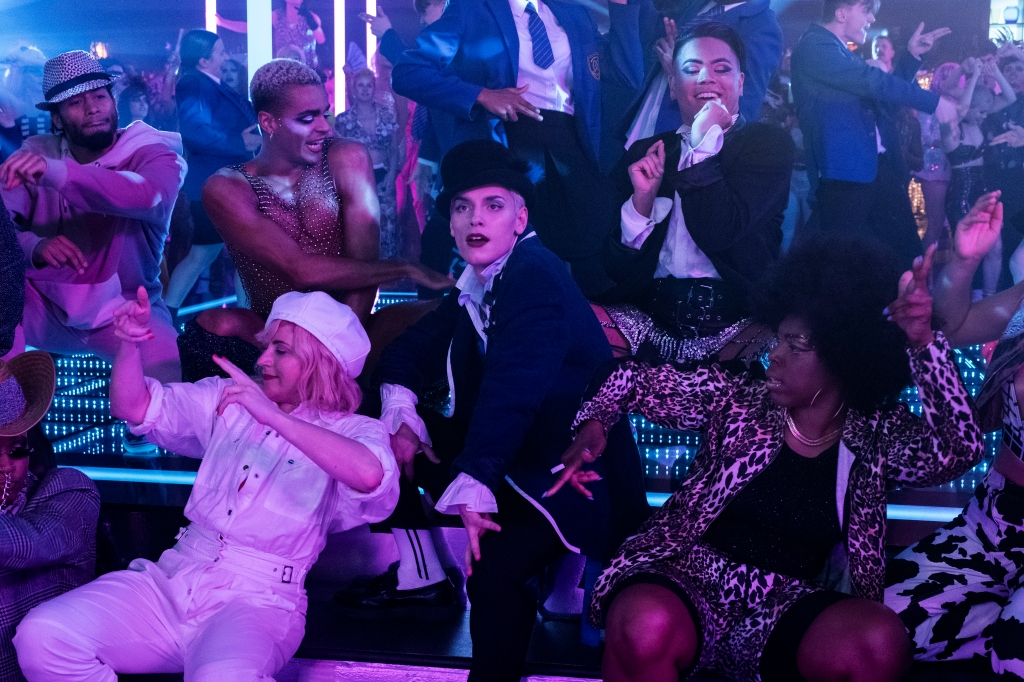 A still from 'Everybody's Talking About Jamie'. Jamie (Max Garwood) isthe focus of the image, sat on nightclub LED-lit stairs wearing a high-fashion school uniform and top hat. He is surrounded by dancers and friends of queer identities.