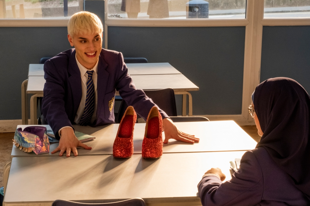 A still from 'Everybody's Talking About Jamie'. Jamie (Max Garwood) is shown in a clasroom, wearing his school uniform, his hair bleach white blonde and eyebrows drawn on with sharp precision. His hands are outstretched on the table, his smile bursting with glee as he shows a pair of red, glittery platform heels sat on the table to best friend Pritti (Lauren Patel), a hijabi girl sat at the other end of the desk.