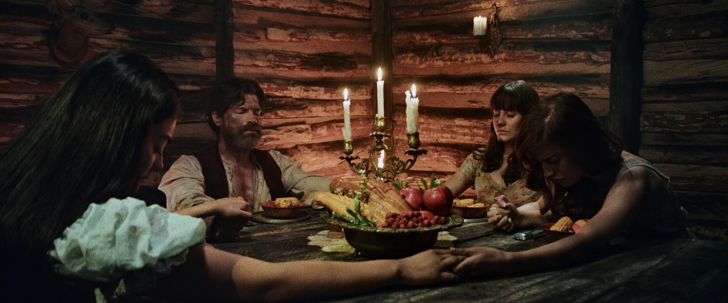 A still from 'Luz: The Flower of Evil'. El Senor (Conrado Onsorio) sits in a wooden cabin, around a table with his daughters Uma (Yuri Vargas), Zion (Sharon Guzman) and Laila (Andrea Esquivel). They hold hands in prayer before a table full of food. A candlestick in the middle of the table is their main light source.