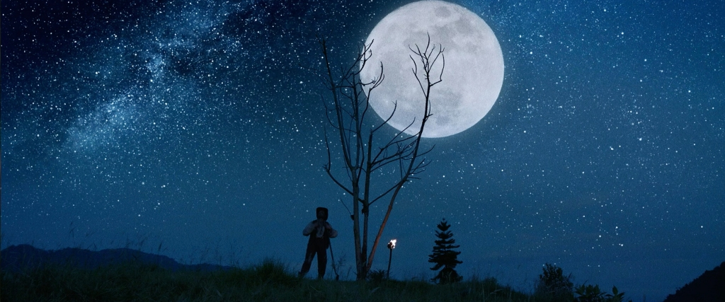 A still from 'Luz: The Flower of Evil'. El Senor (Conrado Onsorio) is shown in a wide shot, standing on top of a grassy hill, next to a bare tree. The scene behind him is extremely beautiful: a blue night sky, smattered with stars and a full moon just behind the tree he stands next to.