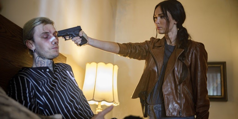 A still from 'Midnight in the Switchgrass'. FBI agent Lombardo (Megan Fox) is to the right of the image, in a hotel bedroom with a gun to a man's (Colson Baker) head. She is wearing a brown leather jacket and grey t-shirt, her dark hair in a side ponytail. The man is sat on the bed, wearing a striped Baseball jersey, blonde hair and neck tattoos, his nose is broken with a bandage on and his face bruised.