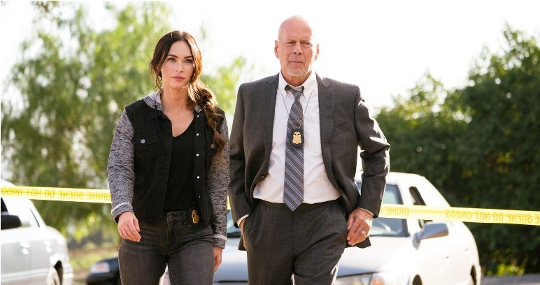 A still from 'Midnight in the Switchgrass'. FBI agents Lombardo (Megan Fox) and Karl (Bruce Willis) are shown in a parking lot, on the other side of some police tape, walking into a crime scene. Lombardo is a white woman in her 30s, wearing grey jeans a black t-shirt and baseball jacket, her dark brown hair swept over in a side ponytail. Karl is wearing a grey suit with a white shirt and striped tie, his police badge hanging round his neck. He is in his 50s and bald.