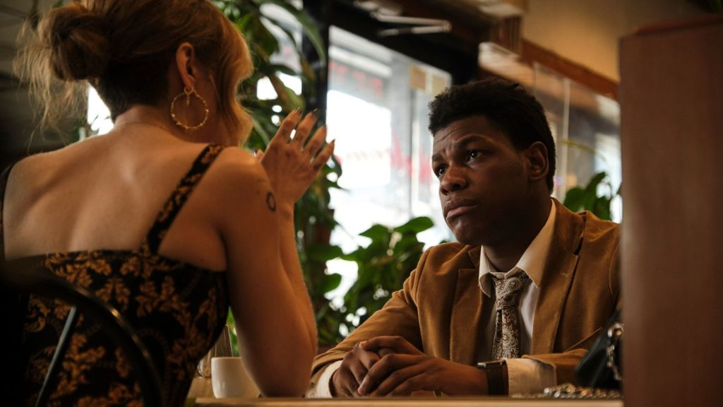 A still from 'Naked Singularity'. Casi (John Boyega) is sat in a restaurant with Lea (Olivia Cookie). The image is shot from low-down, with Lea's back facing us, she is avidly explaining something to him as he looks on with concern.