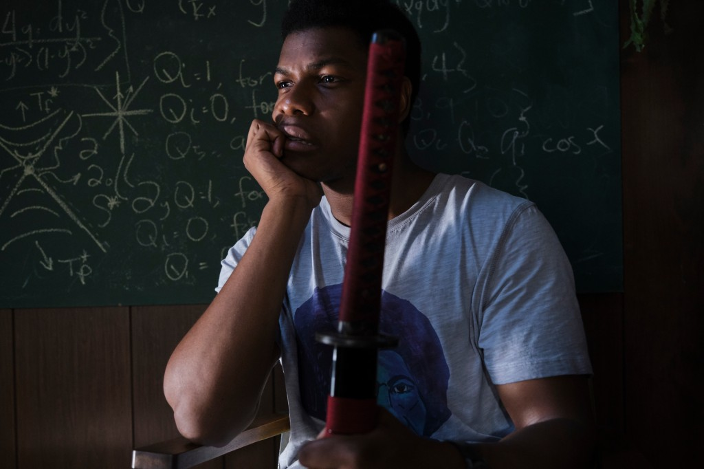 A still from 'Naked Singularity'. Casi (John Boyega) is shown in a mid-shot, sat in a chair, his arm propping up his chin, and his other hand holding a red-bound samurai sword. His is in a classroom environment with equations on a blackboard behind him.