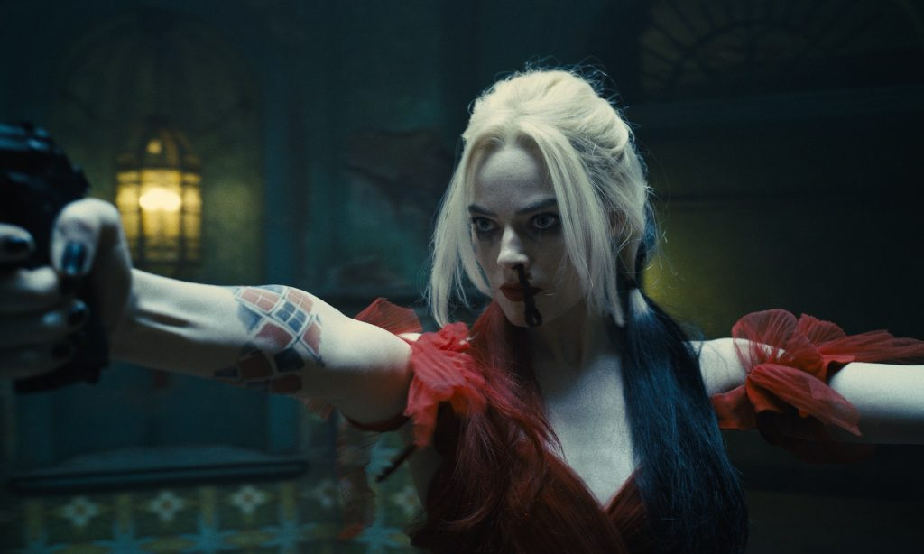 A still from 'The Suicide Squad'. Harley Quinn (Margot Robbie) is pictured in a midshot, just off centre frame, both her arms outstretched holding guns. She is in a dimly lit historic-looking room and wearing a red gown with ruffled sleeves, Her blonde hair is in pigtails hanging low with one bunch dyed red and the other black. Her nose is bleeding profusely.