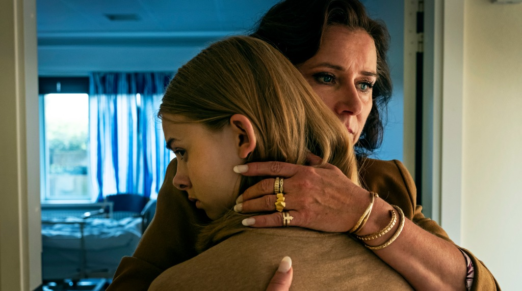 A still from 'Wildland'. Ida (Sandra Guldberg Kampp) is shown in a mid-shot, facing away from the camera, as her Aunt Bodil (Sidse Babett Knudsen) hugs her, her hand on the back of Ida's head. Ida is looking to the side, not fully engaged in the hug, uncomfortable. They are stoof in the doorway to a bedroom.