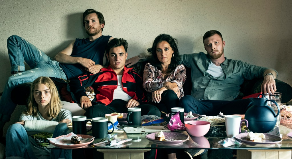 A still from 'Wildland'. Ida (Sandra Guldberg Kampp) is pictured in the bottom left, in a living room, in front of a dirty, dishes-filled coffee table and sat on the floor next to a sofa. On the sofa is her Aunt Bodil (Sidse Babett Knudsen) and her 3 sons. All characters look towards the camera, as if posing for an uncomfortable family portrait.