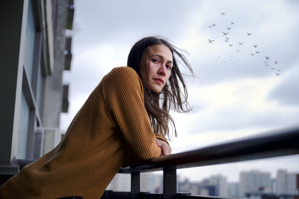 Elle-Maija Tailfeathers stands in the centre of the frame - her mustard yellow jumper contrasts with the grey background. Drone, like birds, fly above her heard as she leans against a rail of a balcony.