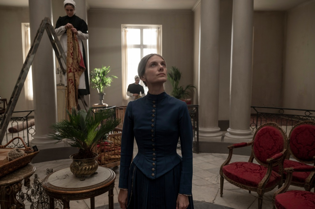 A still from 'The Mad Women's Ball'. Nurse Genevieve (Melanie Laurent) is seen centre frame, watching some maids decorate a grand drawing room for a party. She looks stern but reflective, wearing a blue top and skirt with buttons all down the bodice front.