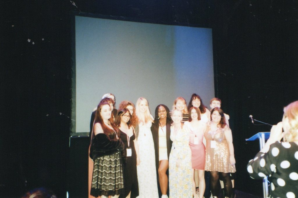 An image taken by the author of the Rianne Pictures team at the Women X Awards ceremony. The 13 women are all huddled in a group posing for photos in an auditorium, a screen is behind them.