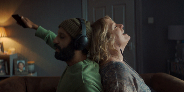 Ali and Ava stand back to back with each other, each wearing a different set of headphones/earphones. Ali had one of stretched out in front of him like he is conducting something unseen, while Ava has her head thrown back in a moment of pure happiness. The room behind them is in semi-darkness, with the focus purely on their faces.
