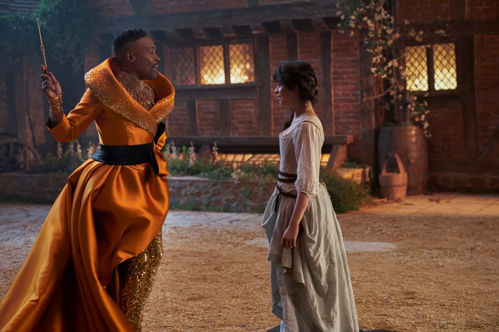 A still from 'Cinderella' (2021). Cinderella (Camilla Cabello) is shown standing with Fab G (Billy Porter), her fairy godmother. Fab G is wearing a beautiful orange silk gown with a grand rolled diamante collar, holding a wand in his hand. Cinderella pales in comparison with her outfit's plainness.